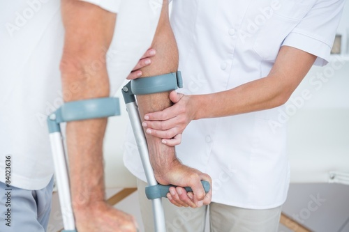 Fotografía  Doctor helping her patient walking with crutch