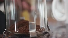 Close Up Of Coffee Grounds Being Added To A Glass French Press Coffeemaker