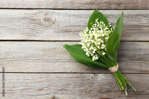 Staande foto Lelietje van dalen Lily of the Valley with leaves on grey wooden background