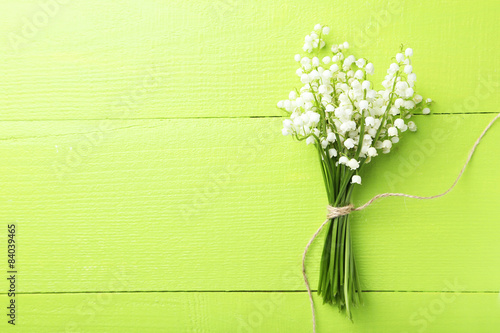 Wall Murals Lily of the valley Lily of the Valley on green wooden background