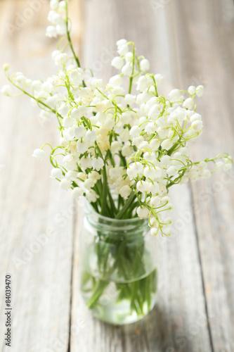 Staande foto Lelietje van dalen Lily of the Valley on grey wooden background