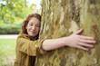Leinwanddruck Bild - schöne junge frau umarmt einen baum