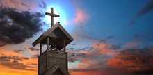 A Bell Tower With Cross At Sun...
