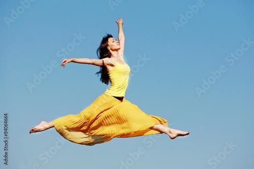 Fotografia  девушка в прыжке на фоне неба в желтом платье