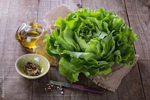 Fotomural Butter lettuce and oil over rustic background