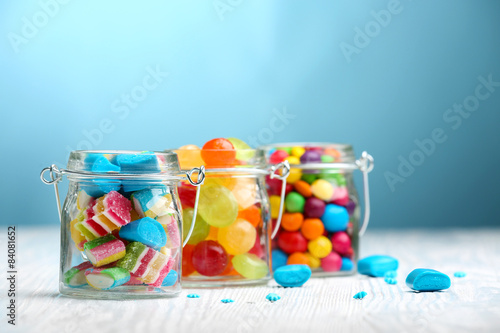 Garden Poster Candy Colorful candies in jars on table on blue background background