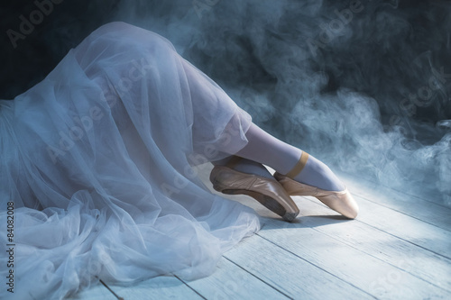 Photo  The feet of a sitting ballerina  in smoke. Dancing legs.