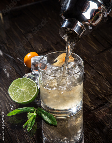 Foto  Pouring a cocktail into glass