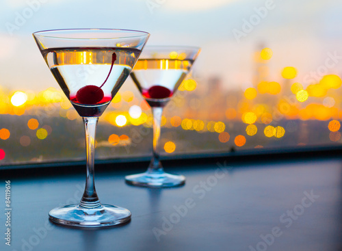 Obraz na plátne Cocktail glasses with city view