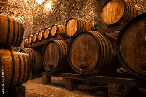 Fotografia  cellar with barrels for storage of wine, Italy