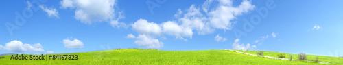 Collina verde all'aperto con nuvole nel cielo blu chiaro