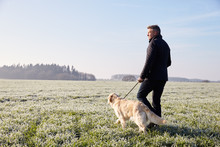 Mature Man Walking Dog In Frosty Landscape