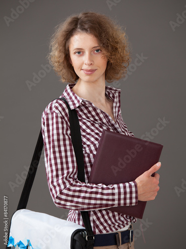 Portrait Of A Young Woman Holding A Book And A Briefcase