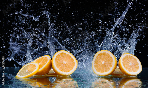 Sliced lemon in the water on black background