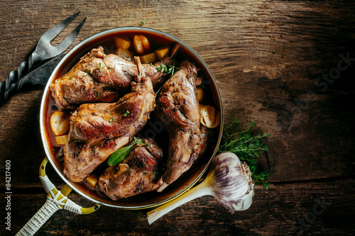 Photo Roasted Rabbit Haunch in Pan on Rustic Wood Table