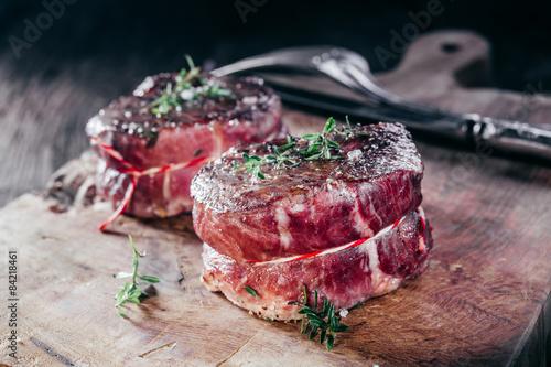 Rare Seasoned Venison Steak Filets on Wooden Board