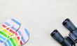 Colorful flip flops and classic binocular
