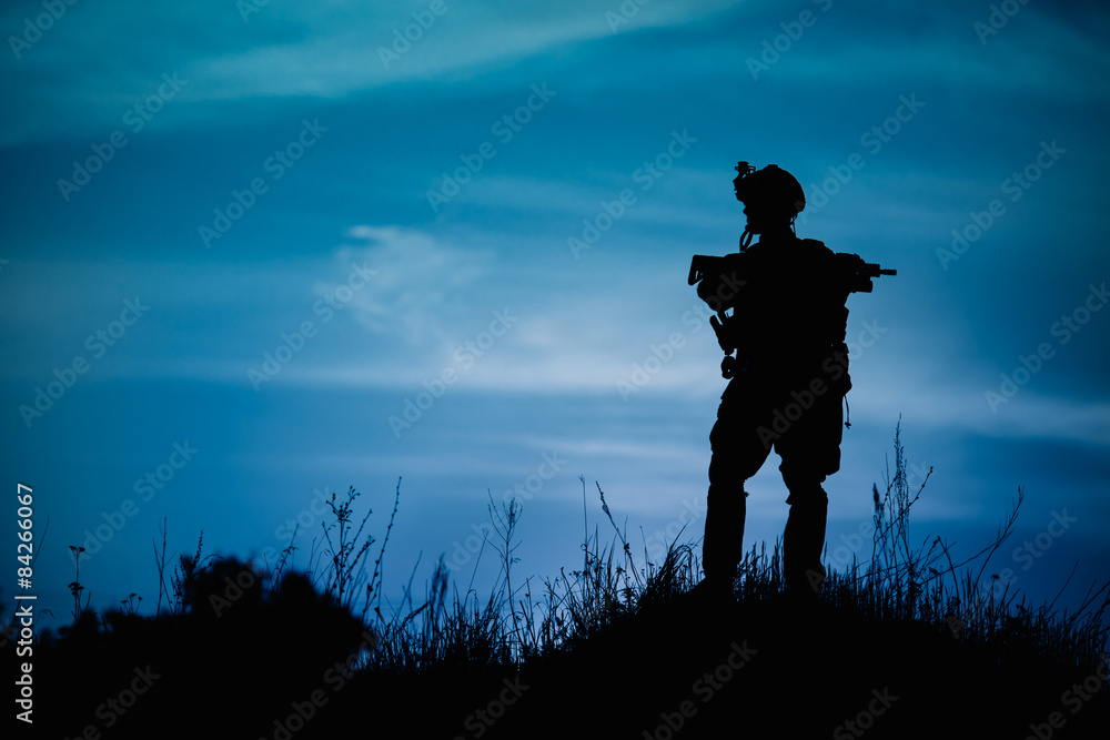 Fototapeta Silhouette of military soldier or officer with weapons at night.