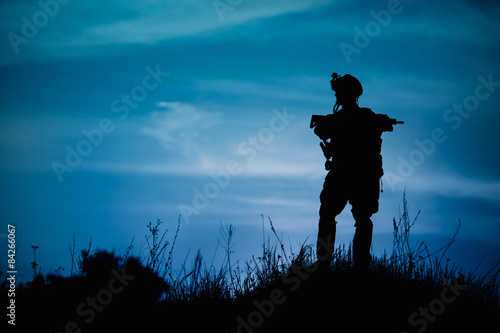 Fotografia  Silhouette of military soldier or officer with weapons at night.