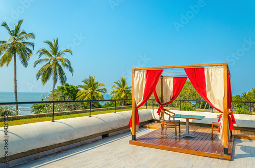 Pergola with tables, chairs and red curtains Wallpaper Mural