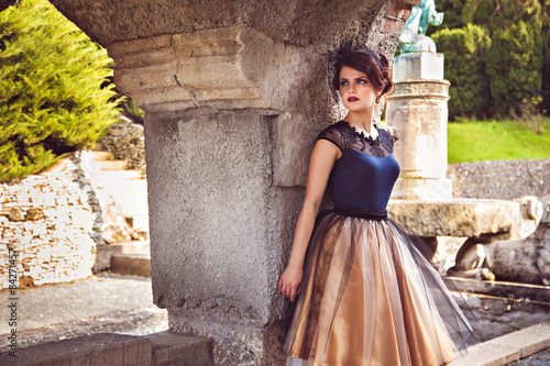 Fotografie, Obraz  Young lady in vintage dress near the column of the castle Roseburg