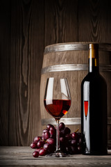 Fototapeta Do winiarni Glass of red wine with bottle and keg standing