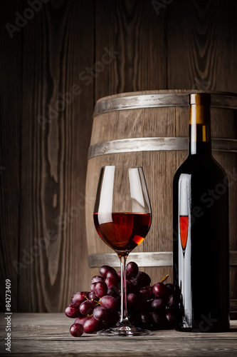 Glass of red wine with bottle and keg standing - 84273409
