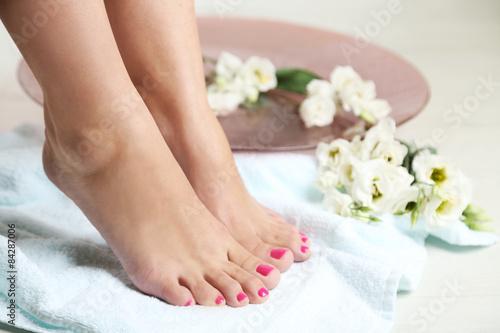 Poster Pedicure Beautiful female legs on towel, on light floor background