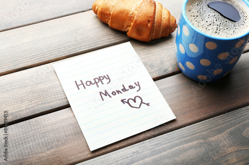 Canvas Prints Coffee beans Cup of coffee with fresh croissant and Happy Monday massage on wooden background