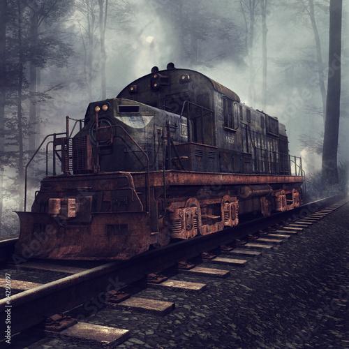 Obrazy na płótnie Canvas Zardzewiała lokomotywa na torach w mglistym lesie
