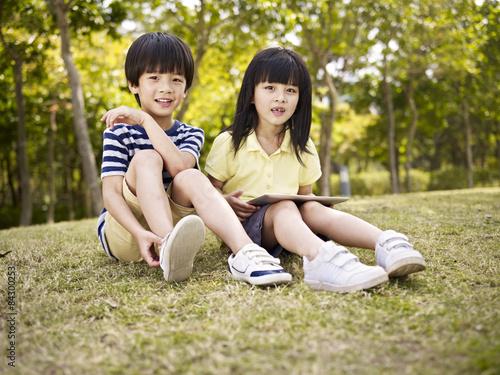Photo  beautiful asian children sitting on grass