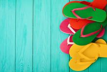 Colorful Flip Flops On Blue Wooden Background