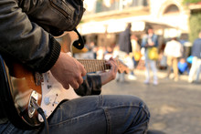 A Street Musician Plays Guitar...