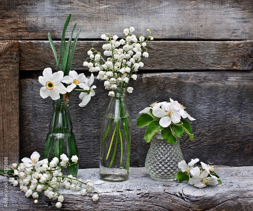 Wall Murals Lily of the valley Small vases and bottles with lilies, daffodils and flowering bra