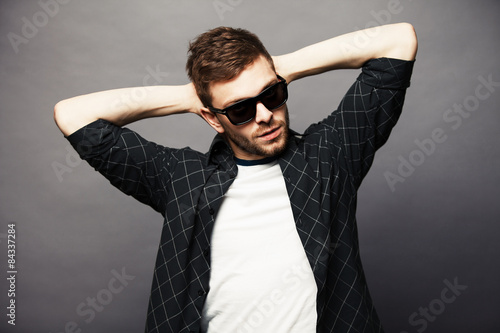 Fotografie, Obraz  Young man in with sunglasses smiles happily with his hands