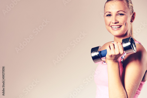 Valokuva  Woman smiling at camera and holding dumbbell.