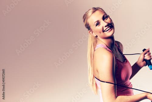 Valokuva  Woman smiling at camera holding a jump rope.