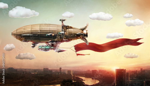 Dirigible with a banner, in the sky over a city. - 84375450