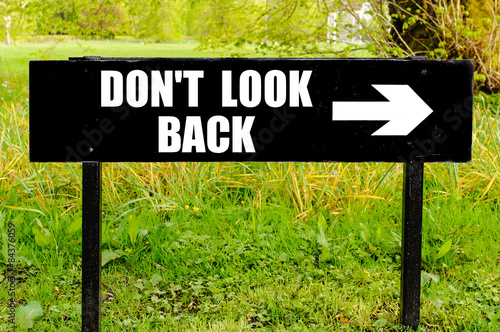 Poster  DO NOT LOOK BACK written on directional black metal sign