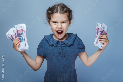 Fotomural teen girl of European appearance holds five denominations of mon