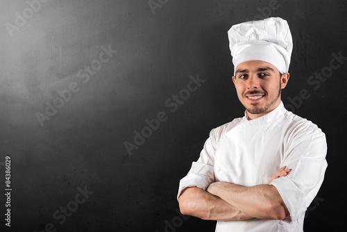 Fotografie, Obraz  cuoco sorridente su fondo lavagna nero