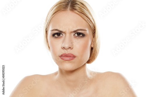scowling young woman on a white background Fototapeta