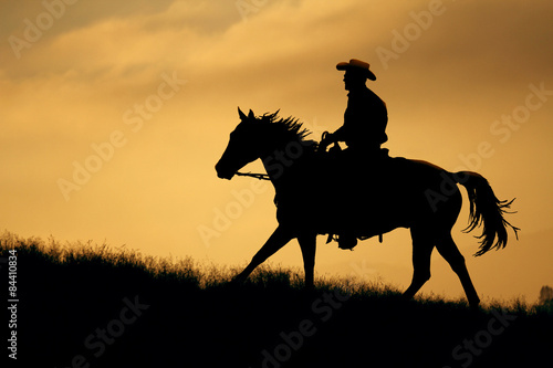 A silhouette of a cowboy and horse walking up a meadow with an  orange and yellow background sky Poster