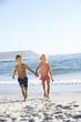 Children running along sandy beach