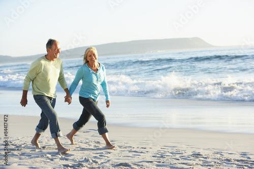 Fotografia  Senior Couple Walking Along Beach