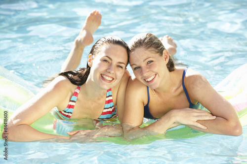 Valokuva  Portrait Of Two Young Women Relaxing In Swimming Pool