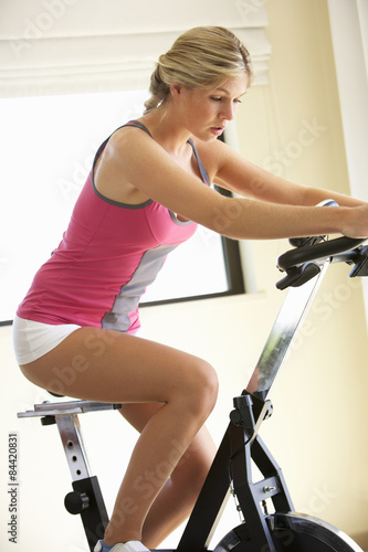 Fotografie, Obraz  Young Woman On Exercise Bike
