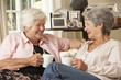 canvas print picture - Two Retired Senior Female Friends Sitting On Sofa Drinking Tea At Home