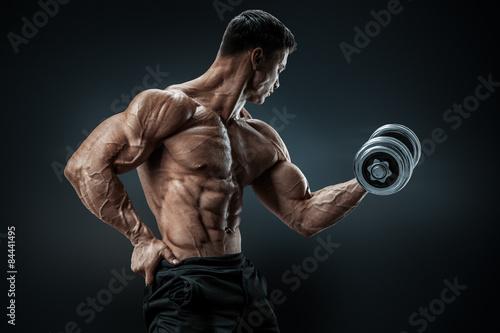 Fotografie, Obraz  Power athletic man bodybuilder doing exercises with dumbbell