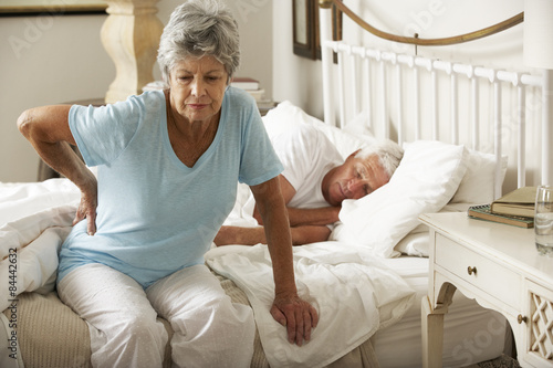 Senior Woman Suffering From Backache Getting Out Of Bed Canvas Print